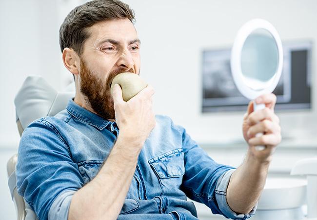 Men biting apple with dental implants
